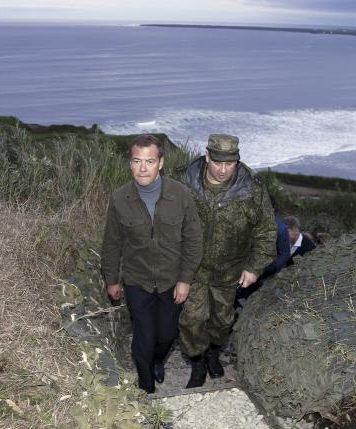 Russia's Prime Minister Dmitry Medvedev (L) inspects a machine gun regiment during his visit to Iturup Island, one of four islands known as the Southern Kurils in Russia and Northern Territories in Japan, August 22, 2015. REUTERS/Dmitry Astakhov/RIA Novosti