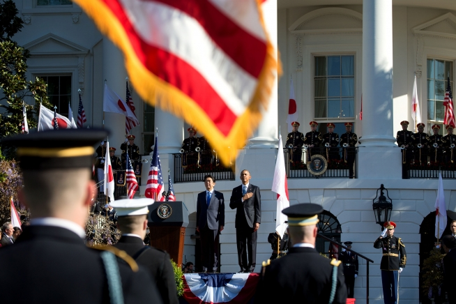 President Barack Obama and Prime Minister Shinzo Abe listen to the U.S. national anthem during Abe's official state visit in April 2015. Public domain photo courtesy whitehouse.gov.
